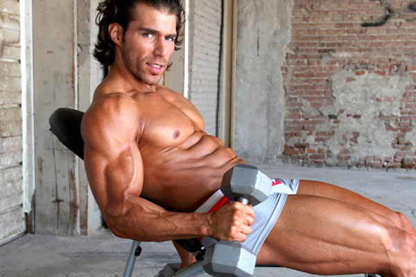 Craig Capurso holding dumbbells in a photo shoot.
