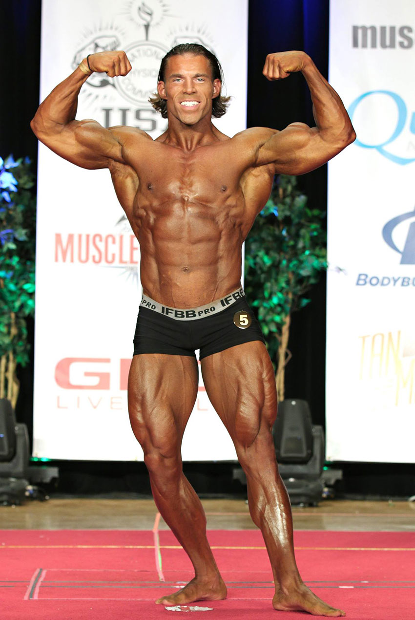 Craig Capurso flexing his arms on the bodybuilding stage.