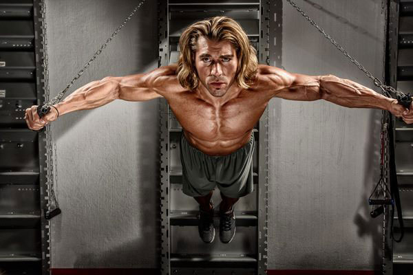 Craig Capurso in a photo shoot holding his weight with cables.