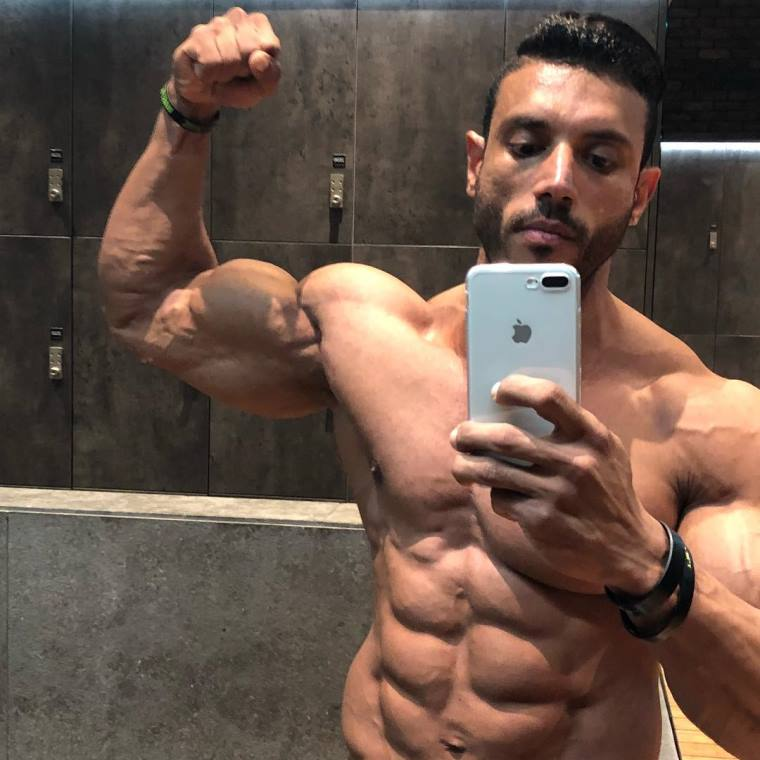 Hany Saeed taking a selfie of himself flexing his biceps and abs
