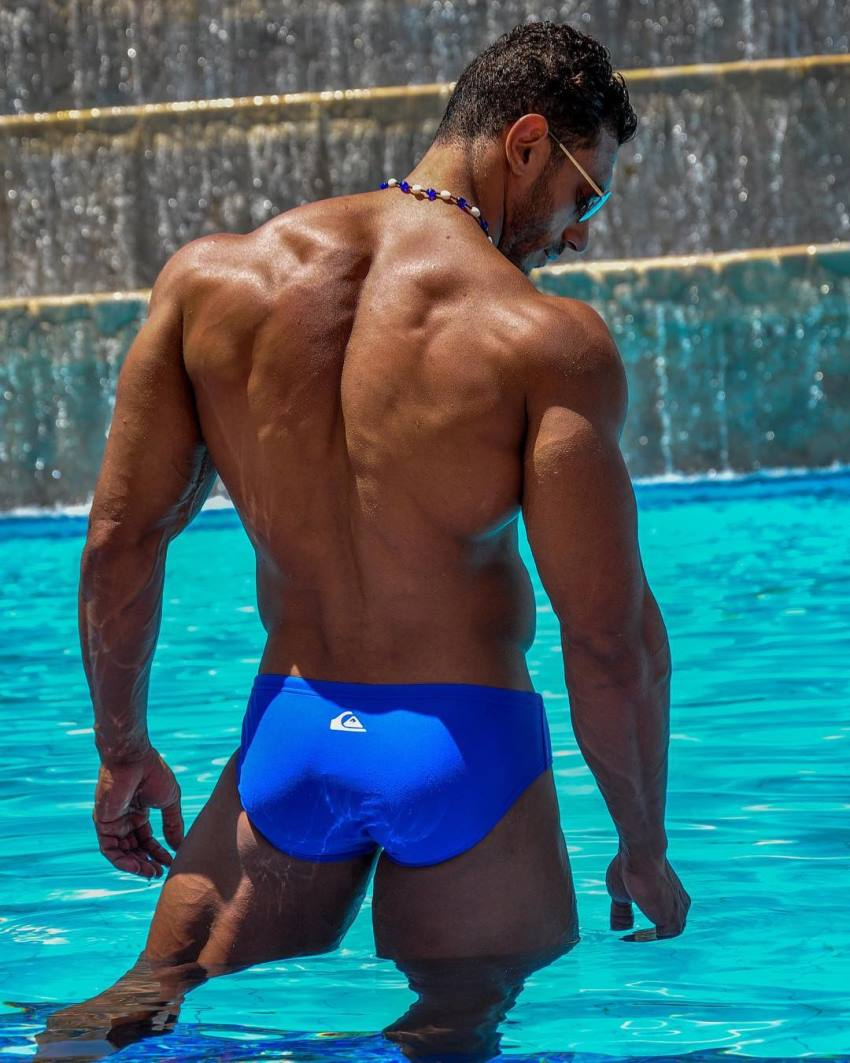 Hany Saeed posing in a pool showing off his wide and muscular back