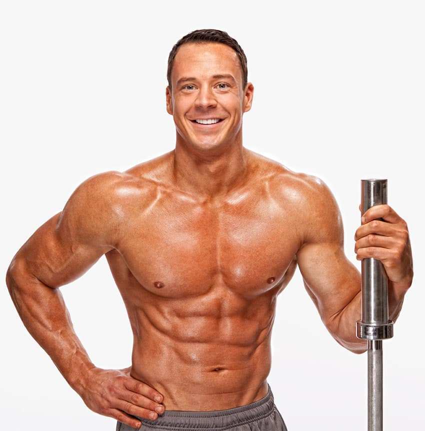 Jeremy Scott smiling at the camera while holding a barbell.