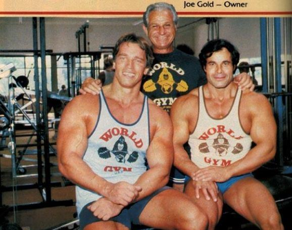 Joe Gold posing for a photo with two bodybuilders in his gym, one of them is Arnold Schwarzenegger