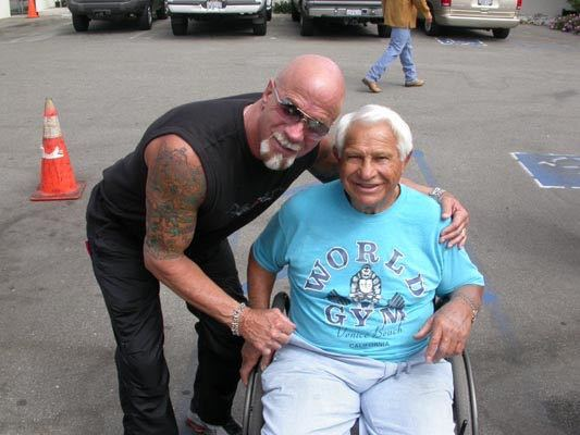 Joe Gold sitting in a wheelchair and posing for a photo with Ric Drasin