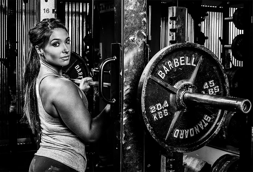 Karina Baymiller in a photo shoot next to a barbell rack.