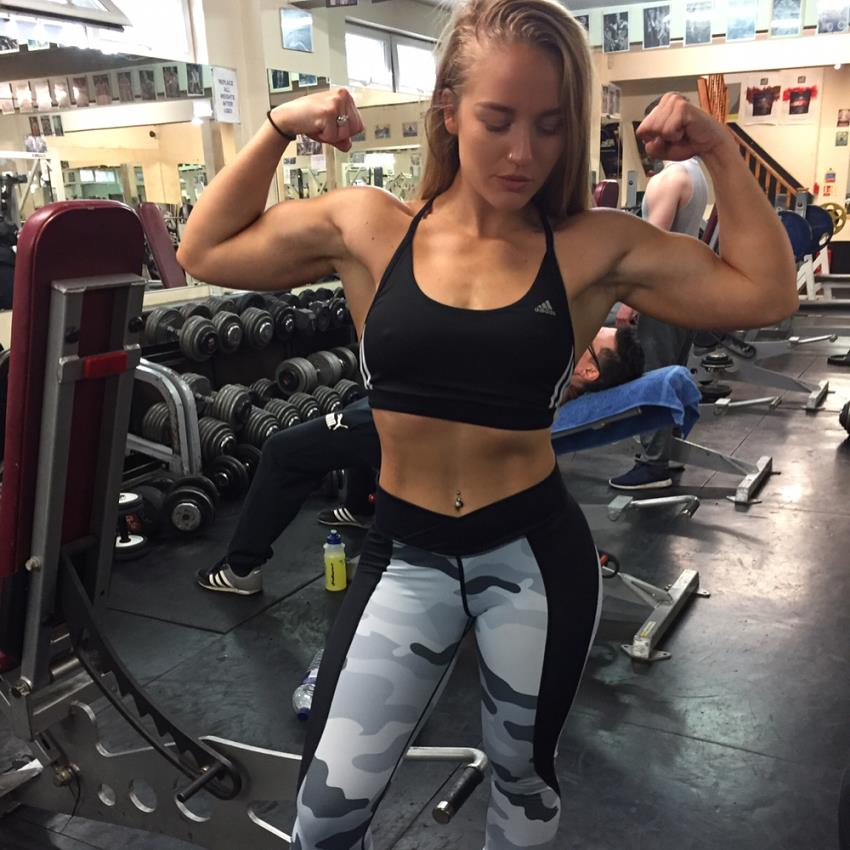 Kashira Whiteley flexing her arms in a gym