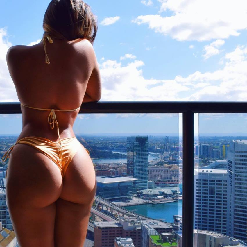 Kate Taylor standing on the balcony in a bikini overlooking a big city with skyscrapers on a sunny day, her glutes looking curvy and toned