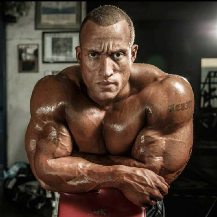 Kevin Jordan being shirtless, looking straight into the camera with a serious look on his face, looking big and muscular