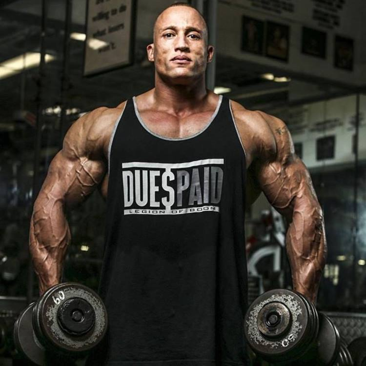 Kevin Jordan posing for a photo in a black tank top and two dumbbells in his hands
