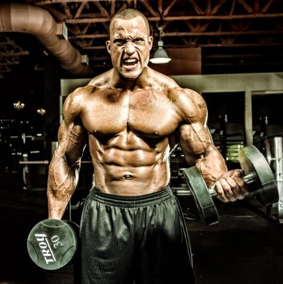 Kevin Jordan lifting heavy dumbbells while being shirtless in a gym