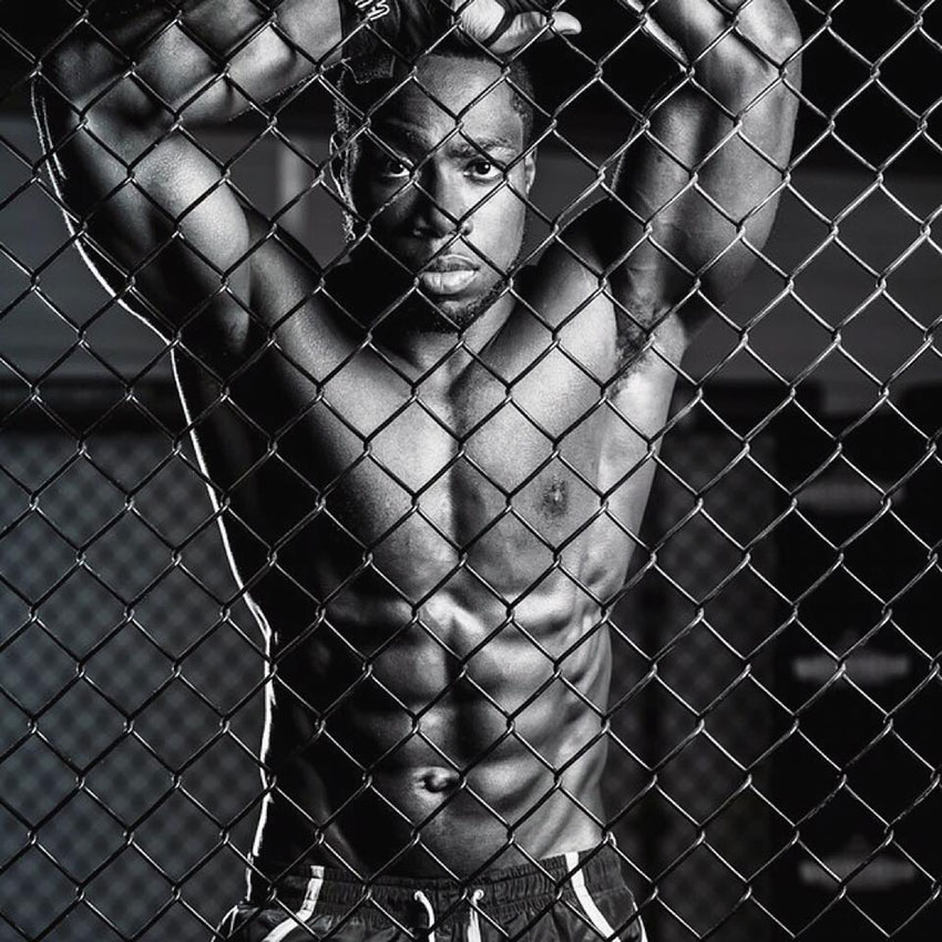 Kizzito Ejam showing off his lean physique in a martial arts cage.