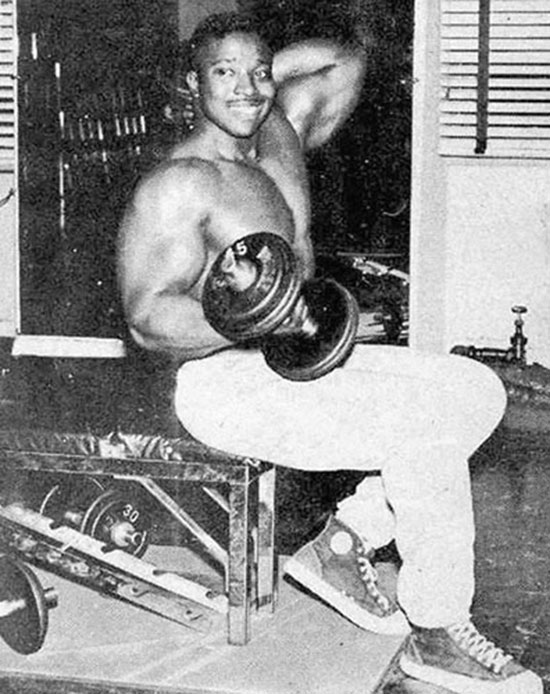 Leroy Colbert in the gym holding a dumbbell.