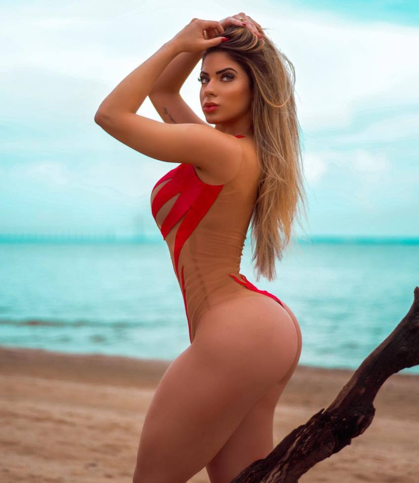 Mariana Castilho posing on a beach in red bikini, looking curvy, lean, and fit