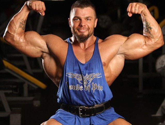 Mike Johnson flexing his biceps in a photo shoot.