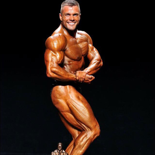 Mike Johnson flexing his bicep on the bodybuilding stage.