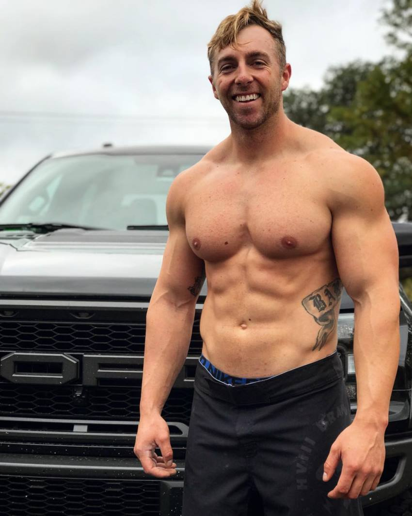 Nick Bare smiling shirtless for a photo, looking fit