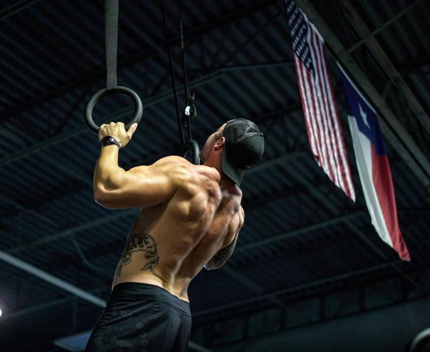 Nick Bare doing pull ups shirtless, looking ripped