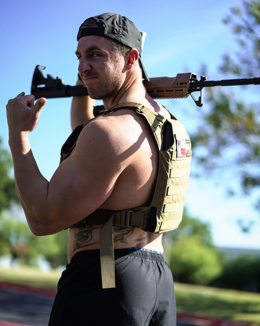 Nick Bare holding a rifle in his arms, looking strong and muscular