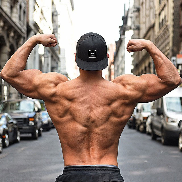 Ryan Hughes showing off his back muscles while flexing his arms.