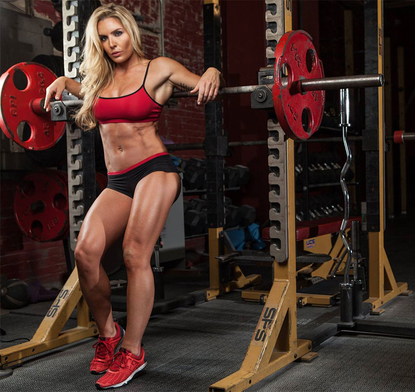 Sarah Grace leaning on a barbell rack in a photo shoot.