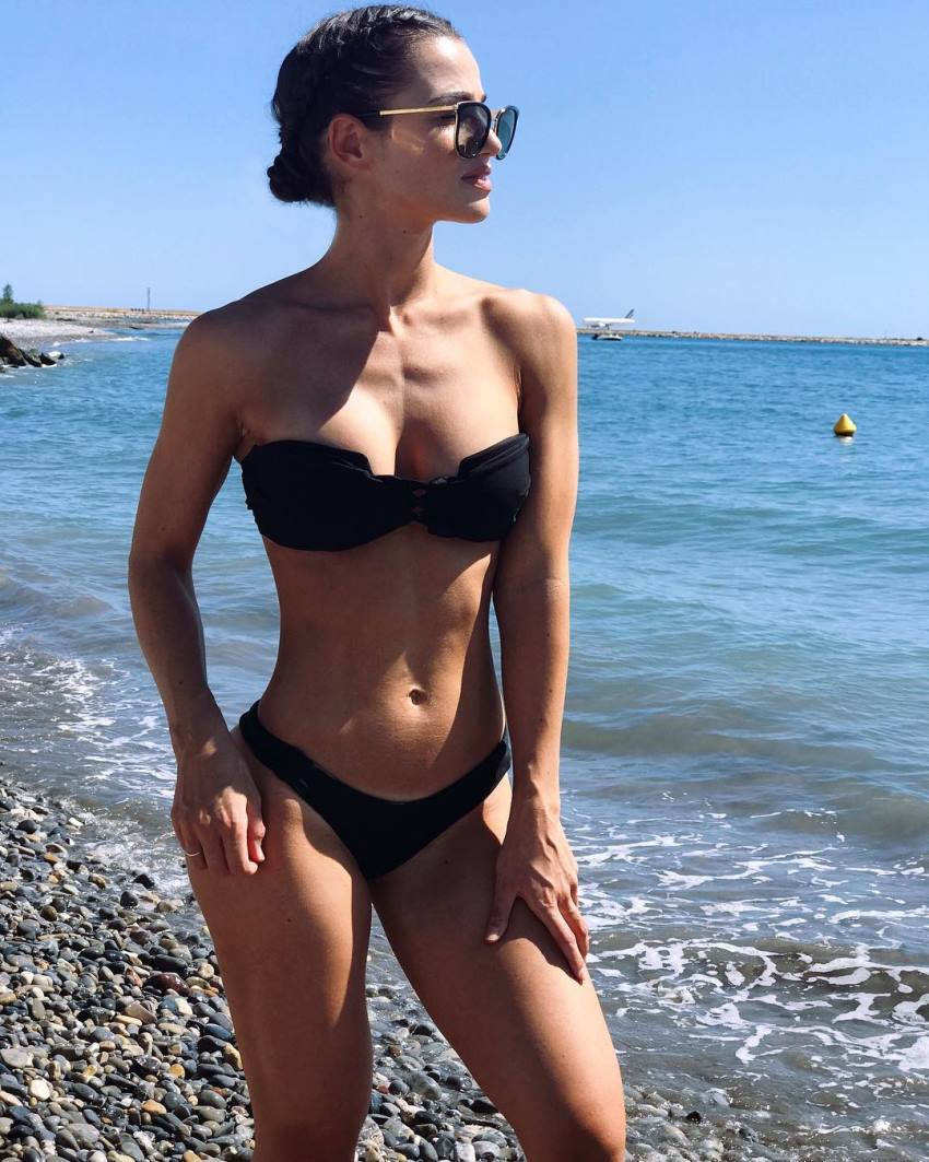 Sissy Mua on the shore in a black bikini, enjoying the sun, looking healthy and fit