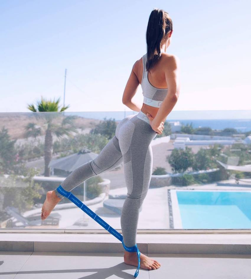 Sissy Mua exercising her glutes with resistance bands, wearing grey leggings