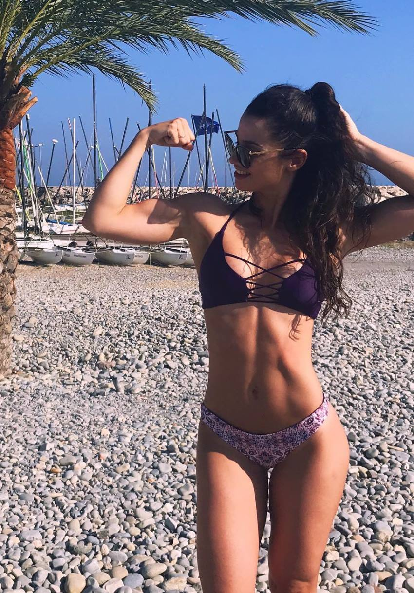 Sissy Mua outdoors wearing a bikini, flexing her biceps