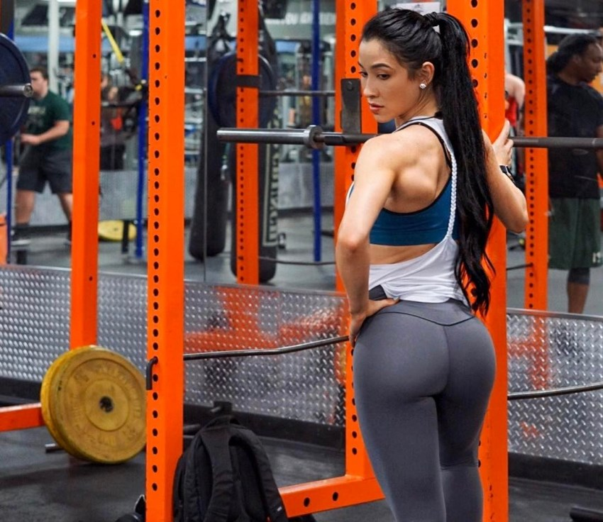 Stephanie Buttermore standing by a squat rack in a gym, looking healthy and fit