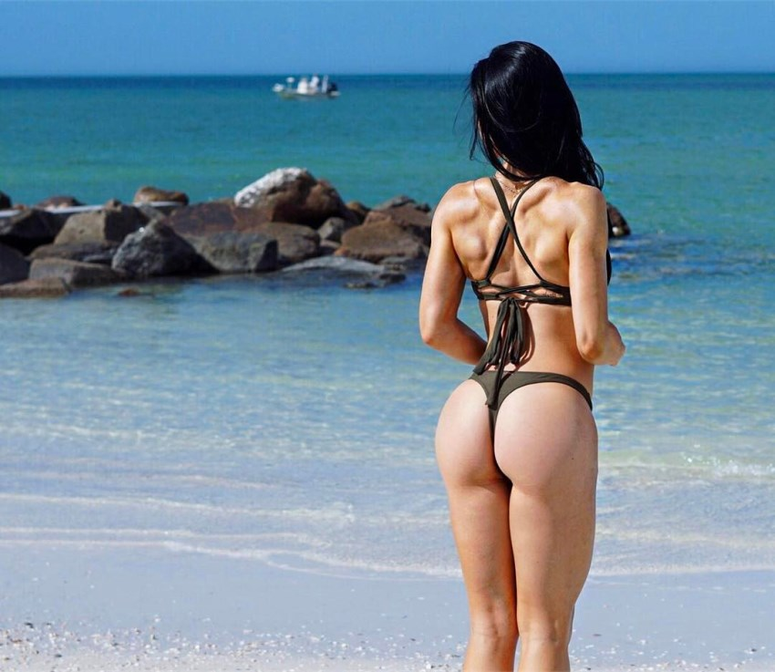 Stephanie Buttermore standing on the shore looking at the sea, showcasting her attractive glutes