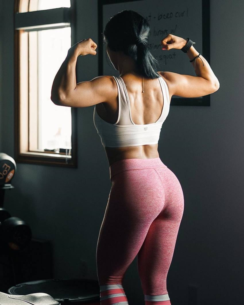 Stephanie Buttermore flexing her biceps, back, and glutes for a photo