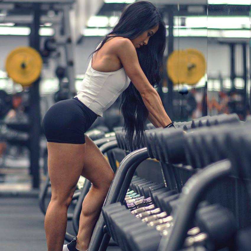 Stephanie Buttermore leaning against the dumbbell rack in a gym