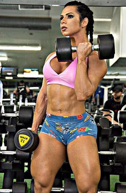 Suelen Bissolat doing biceps curls in a gym, looking fit and curvy