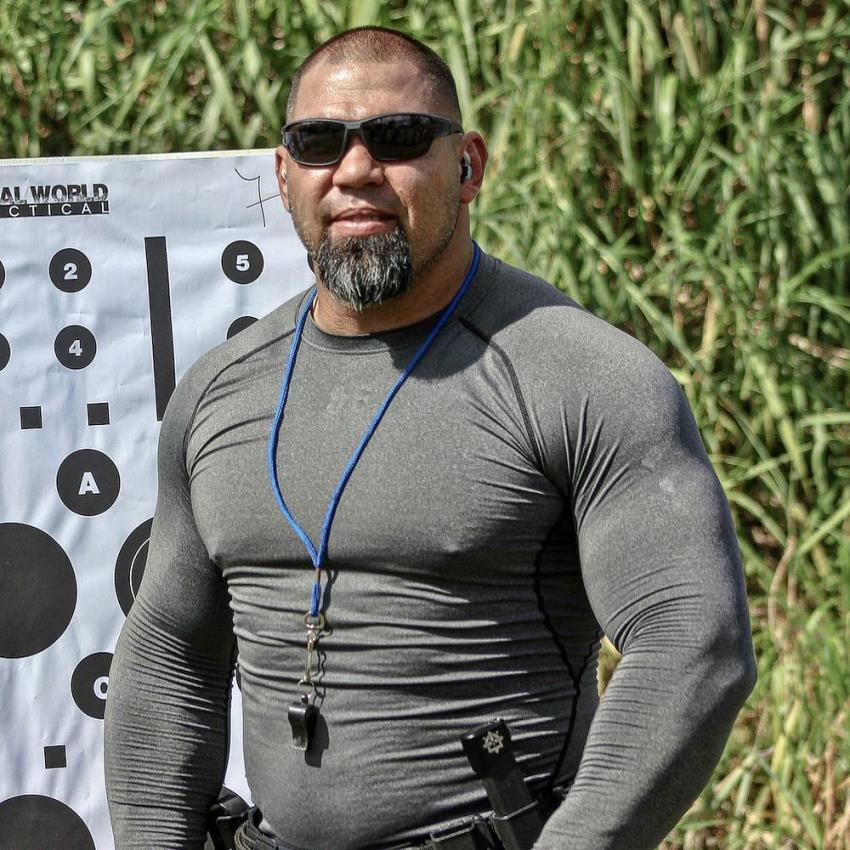 Tony Sentmanat posing for a photo, wearing black sunglasses, looking big and muscular