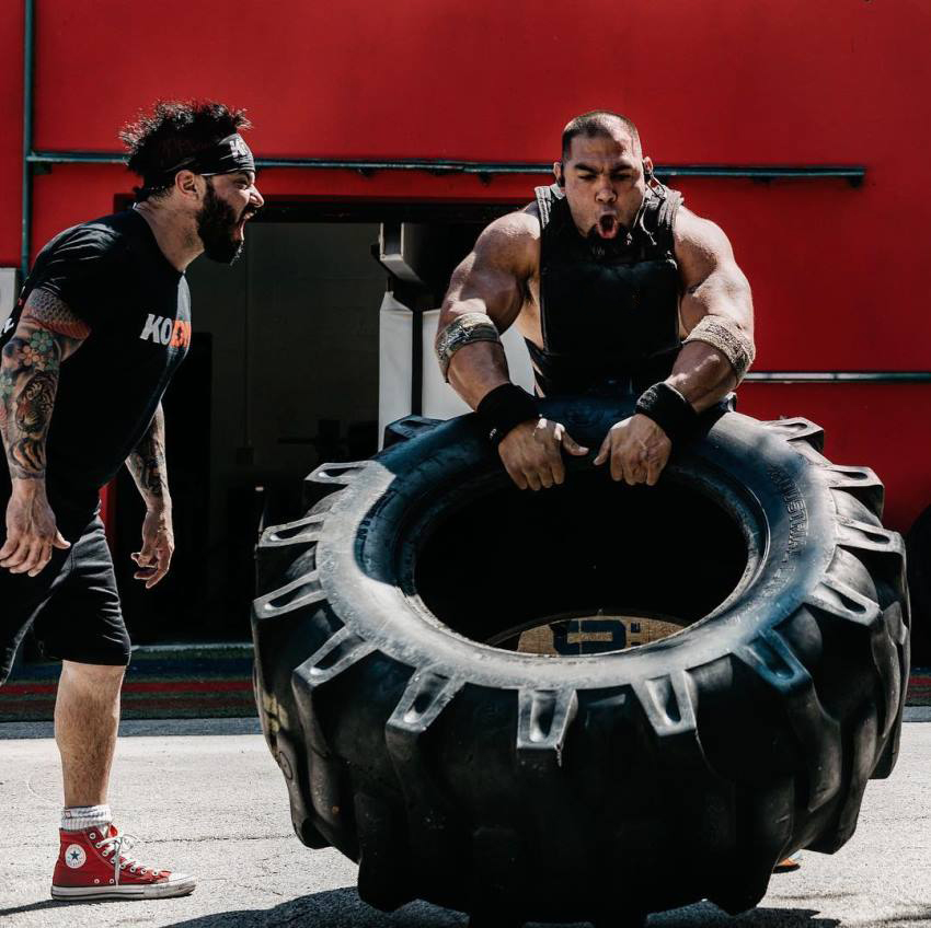 Tony Sentmanat flipping a big heavy tire while another man is motivating him by yelling at him