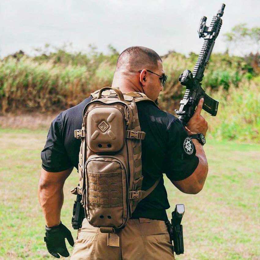 Tony Sentmanat wearing a combat-equipment backback along with a rifle in his arm, looking big and muscular