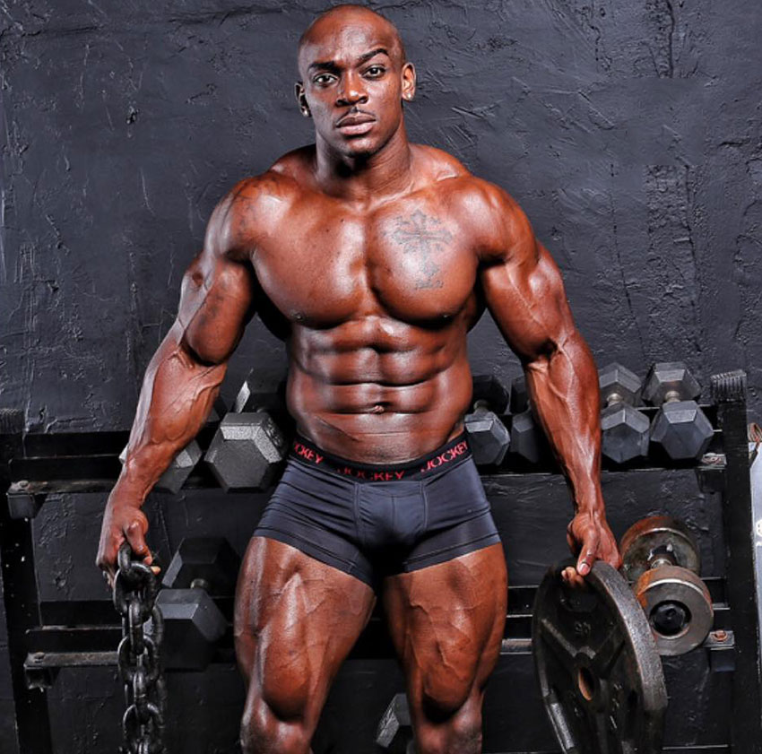 Tyrone Ogedegbe holding a chain and a weight plate in a photo shoot.
