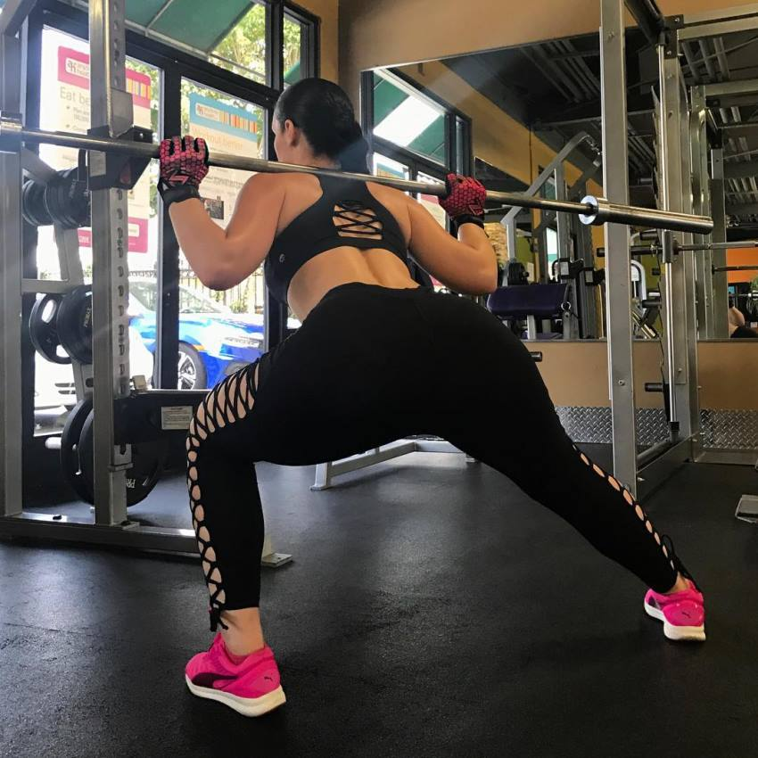 Viktoria Kay doing barbell lunges in a gym