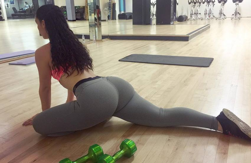 Viktoria Kay stretching in a yoga room, wearing grey leggings, her glutes looking amazing