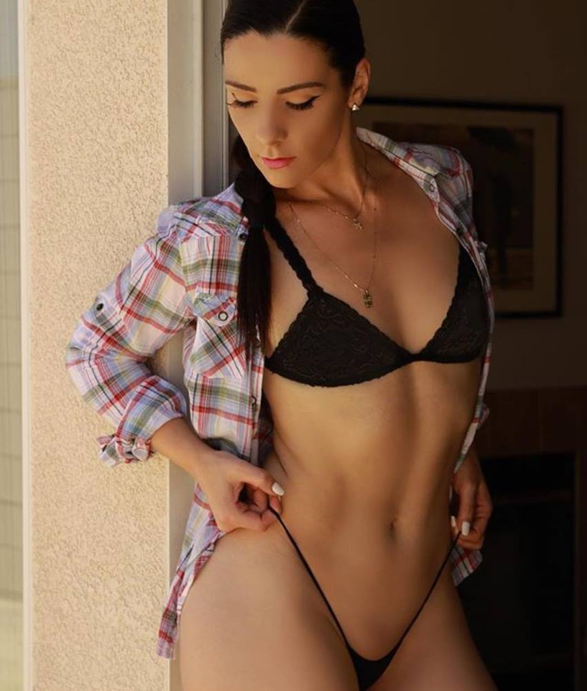 Viktoria Kay posing for a photo in a black bikini and plaid shirt, looking fit and lean