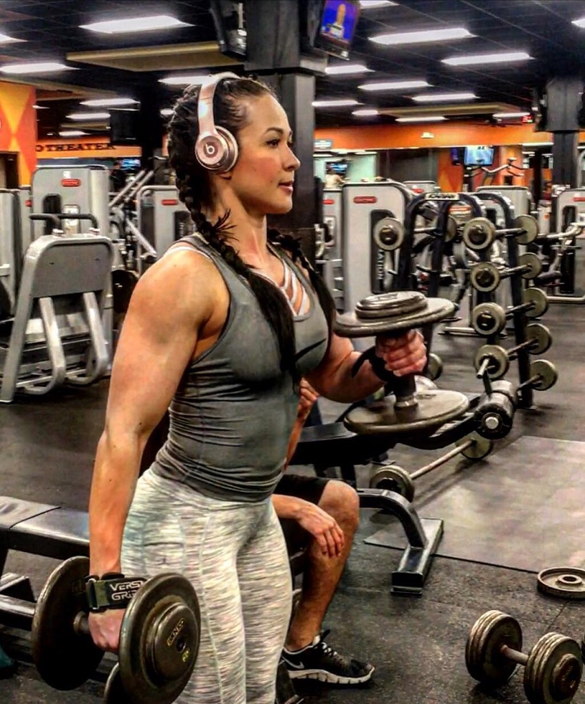 Alexis Mariah Avina doing dumbbell curls in the gym with headphones on, looking fit and lean