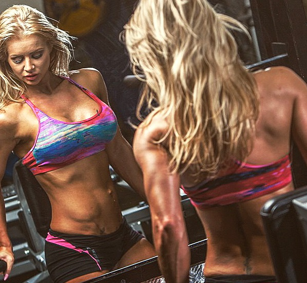 Charlene Borley lifting dumbbells in a gym looking lean and fit