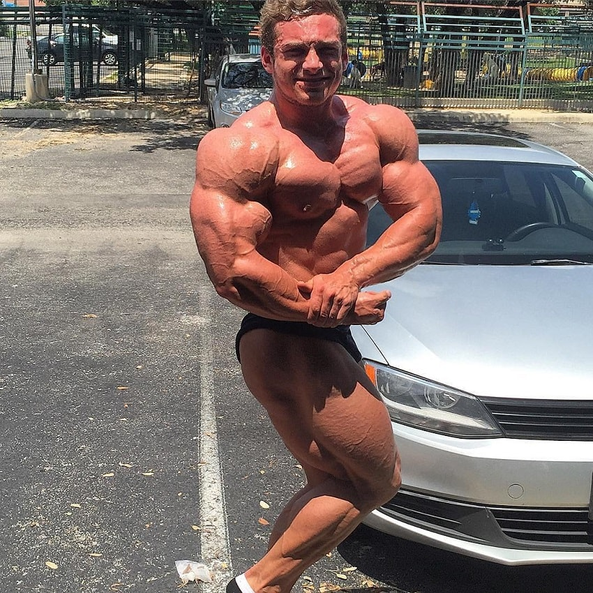 Cody Montgomery doing a shirtless side chest pose outdoors by his car