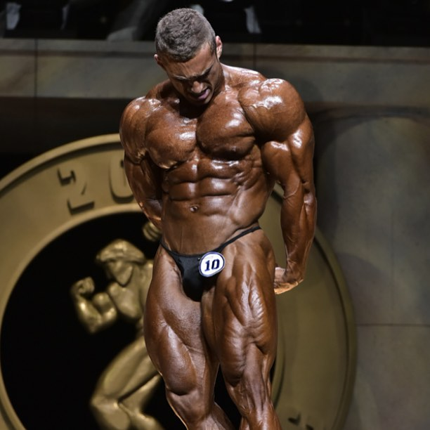 Cody Montgomery posing on a bodybuilding stage, looking big and muscular