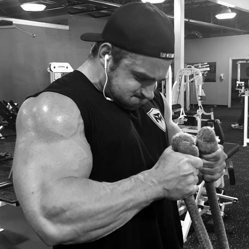 Cody Montgomery doing cable hammer curls his arms looking huge