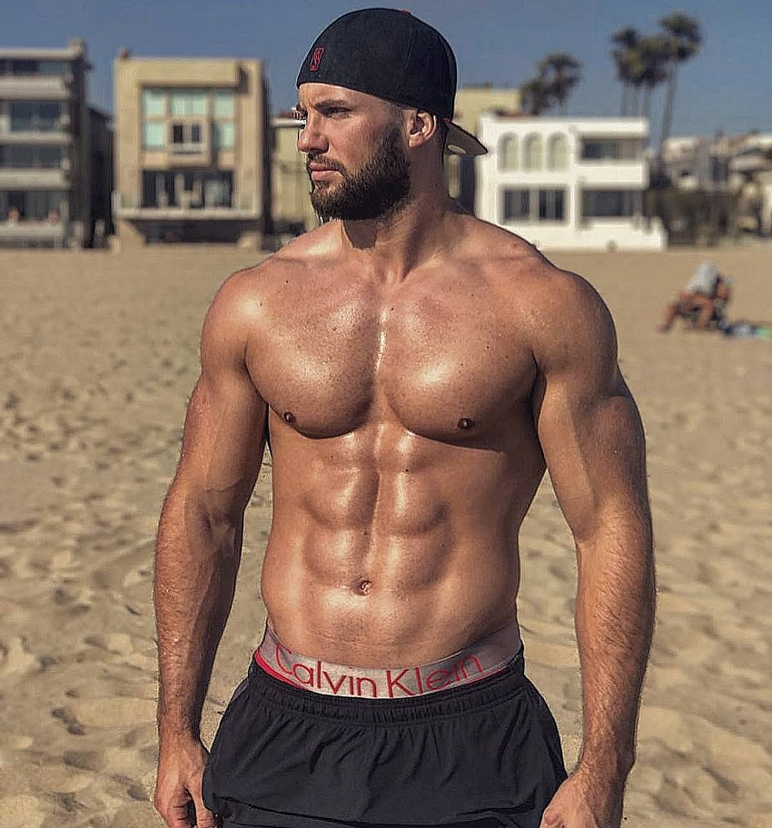 Florian Munteanu posing shirtless on a beach looking fit and lean