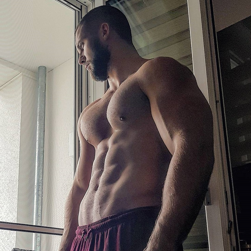Florian Munteanu standing by the balcony without a shirt looking ripped and muscular
