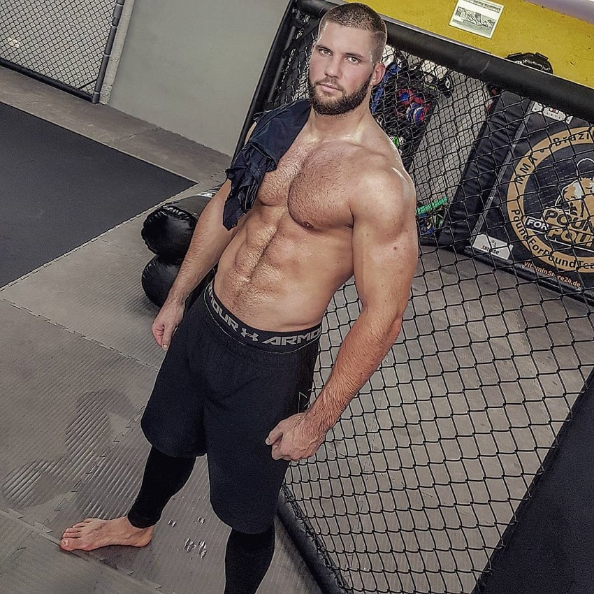 Florian Munteanu posing shirtless for a photo showcasing his aesthetic physique