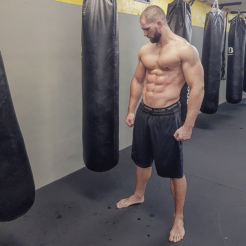 Florian Munteanu standing shirtless by a boxing bag looking big and lean
