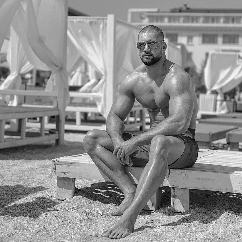 Florian Munteanu sitting shirtless on a beach looking fit and lean