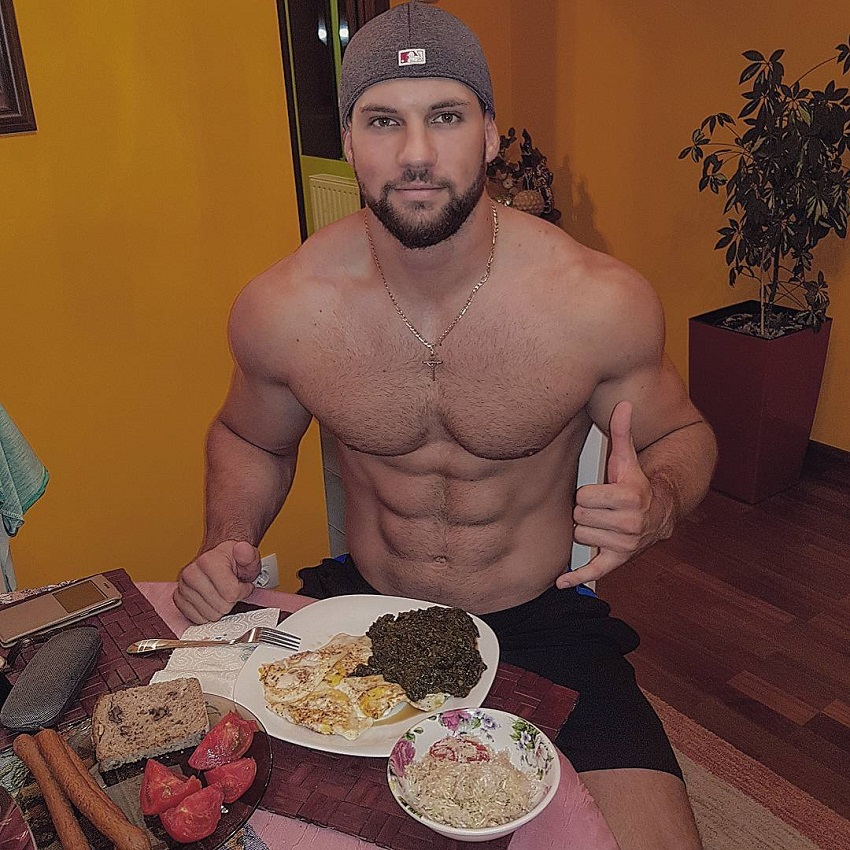 Florian Munteanu sitting shirtless having a meal